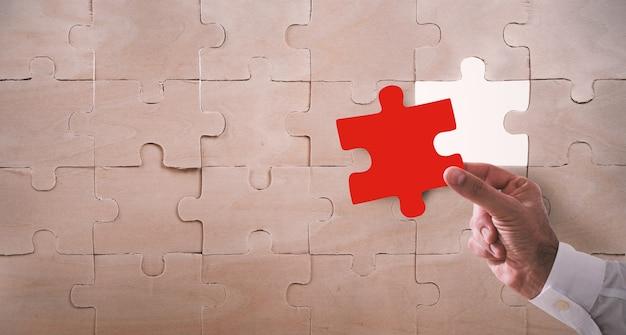 Homme d'affaires terminer un puzzle en insérant une pièce manquante