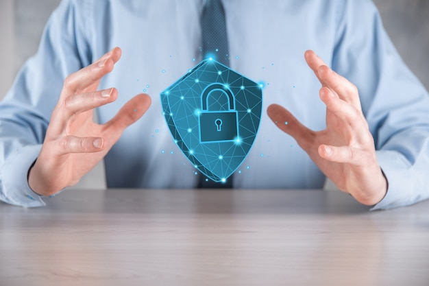 Un homme d'affaires tient un bouclier de polygone poly faible avec une icône de cadenas. concept de système d'accès sécurisé. garantie financière d'entreprise pour l'investissement. concept antivirus. sécurité de la technologie. réseau de protection, données sécurisées.