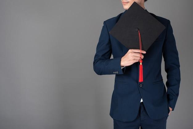 Homme d'affaires tient un chapeau de remise des diplômes, concept de l'éducation commerciale