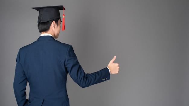 Homme d'affaires tient un chapeau de remise des diplômes, concept d'éducation des entreprises