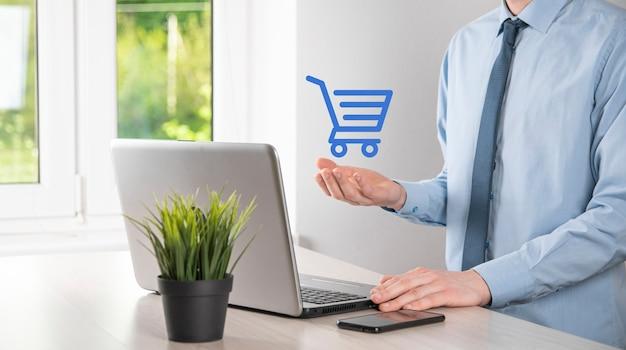 L'homme d'affaires tient dans la main l'icône du panier. shopping en ligne concept.basket hologramme. achats en ligne, application de boutique en ligne dans un smartphone. marketing numérique en ligne