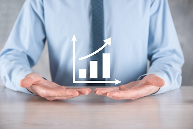 L'homme d'affaires tient le dessin sur le graphique croissant de l'écran, la flèche de l'icône de croissance positive.