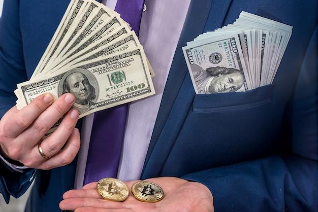 L'homme d'affaires tient le dollar et le bitcoin dans la main