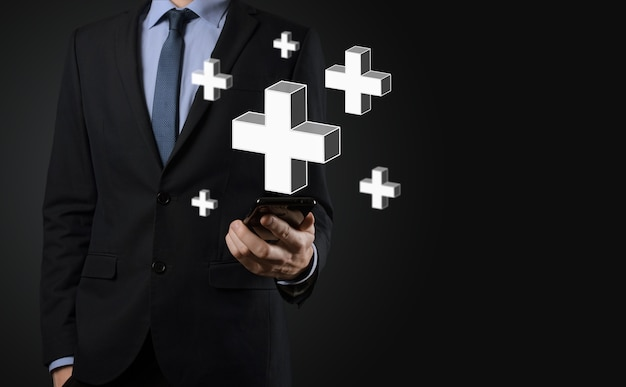 L'homme d'affaires tient l'icône 3d plus, l'homme tient dans la main une offre positive telle que le profit, les avantages, le développement, la rse représentée par le signe plus. la main montre le signe plus
