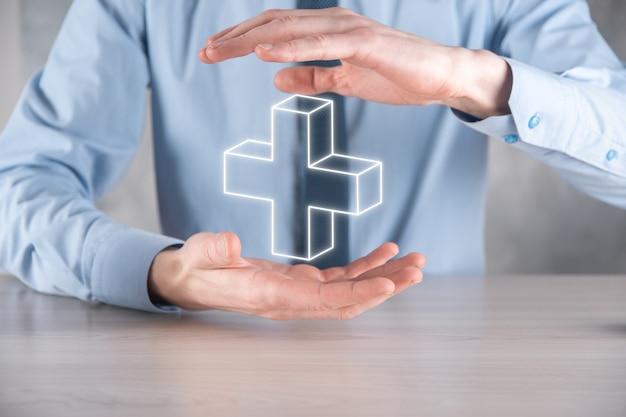L'homme d'affaires tient l'icône 3d plus, l'homme tient dans la main une offre positive telle que le profit, les avantages, le développement, la rse représentée par le signe plus. la main montre le signe plus.