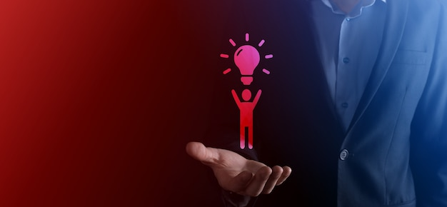 L'homme d'affaires tient l'icône de l'homme avec des ampoules, des idées de nouvelles idées avec une technologie innovante et de la créativité. créativité conceptuelle avec des ampoules qui brillent de mille feux.