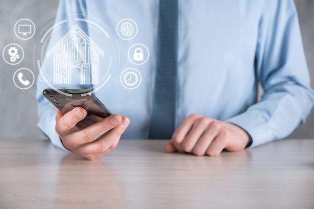 L'homme d'affaires tient l'icône de la maison. concept d'application de maison intelligente contrôlée, de maison intelligente et de domotique. conception de circuit imprimé et personne avec un téléphone intelligent. concept de réseau internet de technologie d'innovation.