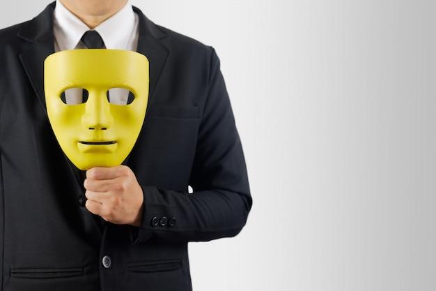 Homme d'affaires tient le masque à la main sur fond gris