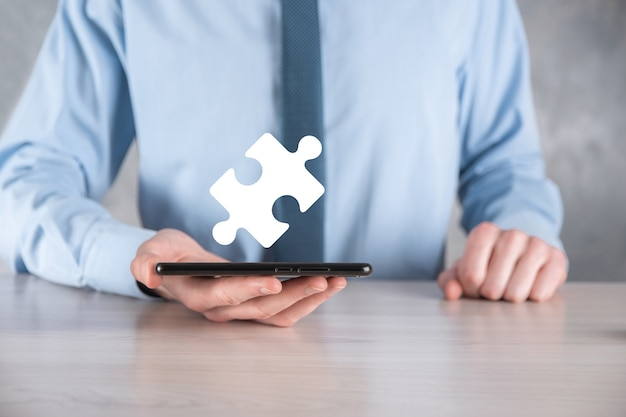 Homme d'affaires tient un morceau de puzzle dans ses mains.le concept de coopération, de travail d'équipe, d'aide et de soutien en entreprise.