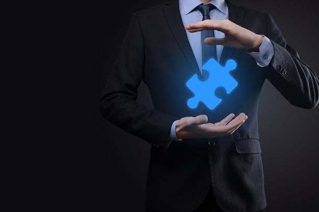 Homme d'affaires tient un morceau de puzzle dans ses mains.