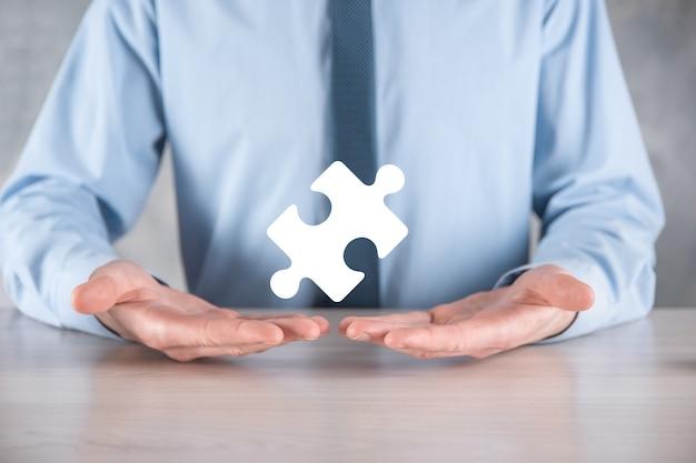 Homme d'affaires tient un morceau de puzzle dans ses mains