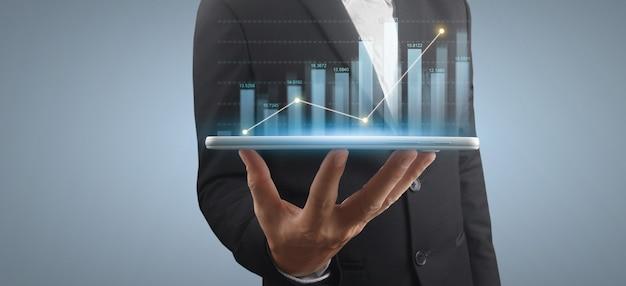 L'homme d'affaires tient une tablette avec un hologramme graphique croissant sur fond gris