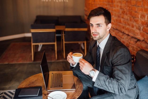 L'homme d'affaires tient une tasse de café au café et regarde au loin