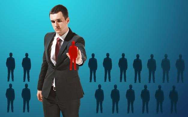 Homme d'affaires touchant la barre de recherche vide ou l'écran virtuel du capteur sur le mur bleu du studio