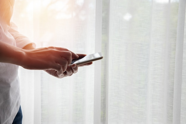 Homme d'affaires touchant smartphone, tablette sur fond de rideau blanc de fenêtres.