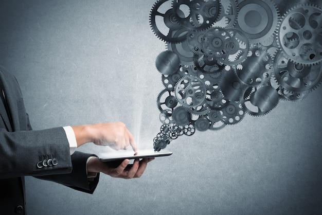 Homme d'affaires touche un écran de tablette avec mécanisme d'engrenages