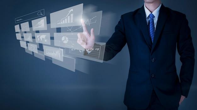 Homme d'affaires touche à l'écran virtuel, fond gris en studio