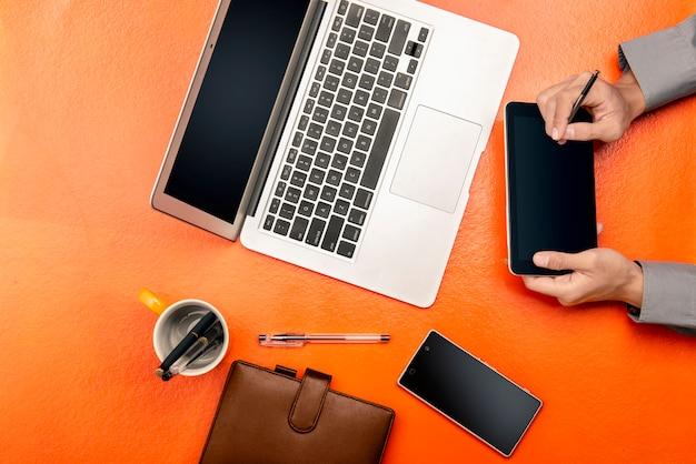Homme d'affaires travaillant à l'aide d'une tablette numérique, d'un ordinateur portable et d'un téléphone mobile