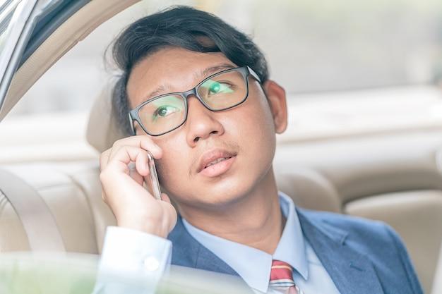 Homme d'affaires travaillant à l'arrière d'une voiture