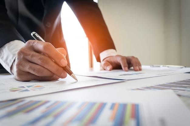 Homme d'affaires travaillant au bureau avec des documents de données graphiques sur son bureau.
