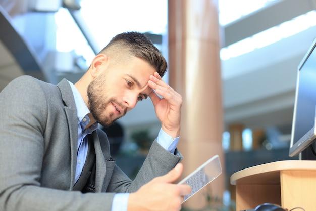 Homme d'affaires travaillant au bureau avec une tablette transparente et un ordinateur pc.