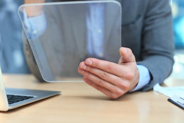 Homme d'affaires travaillant au bureau avec tablette transparente et ordinateur portable.