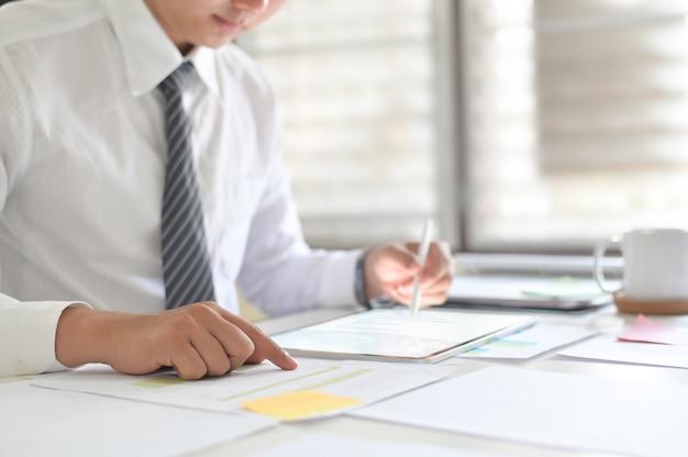 Homme d'affaires travaillant avec des données d'analyse sur tablette numérique.