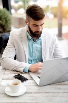 Homme d'affaires travaillant à l'extérieur du bureau surfant sur internet en ligne à la recherche d'achats.