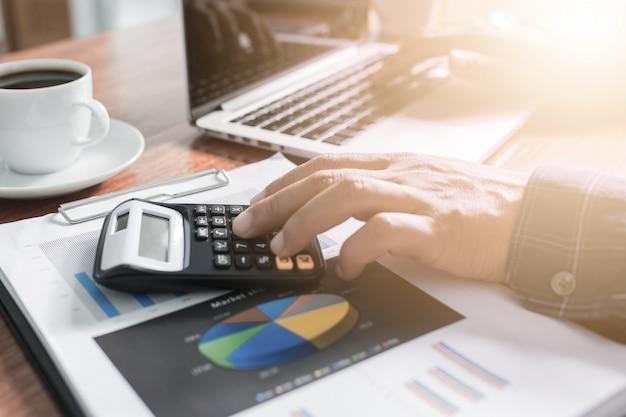 Homme d'affaires travaillant avec un lieu de travail moderne avec un ordinateur portable sur une table en bois, main de l'homme sur un clavier d'ordinateur portable pour le travail à domicile,