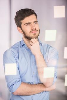 Homme d'affaires travaillant sur un nouveau projet avec de nombreuses notes autocollantes.
