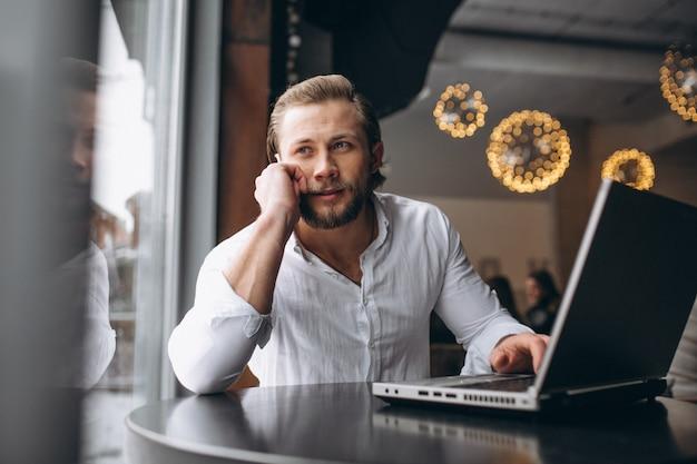 Homme d'affaires travaillant sur ordinateur dans un café