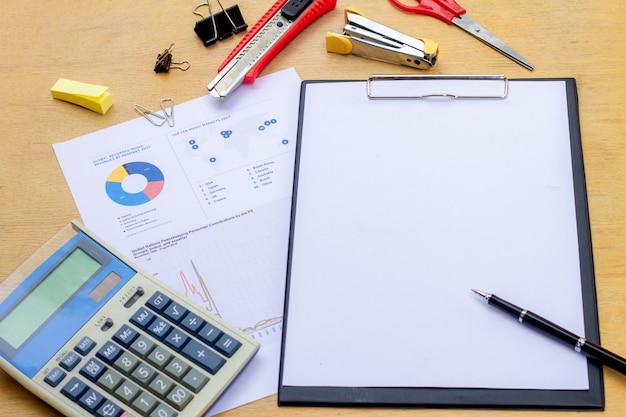 Homme d'affaires travaillant sur un ordinateur portable au bureau avec des documents et autres objets autour