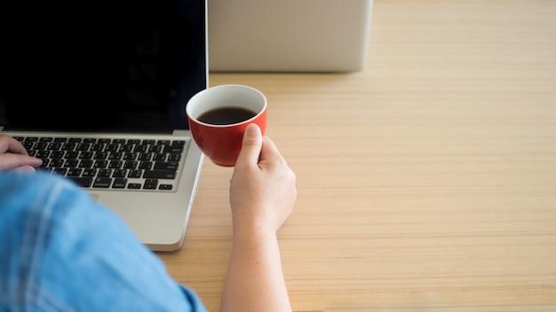Homme d'affaires travaillant avec un ordinateur portable et consommant du café avec copyspace au bureau.