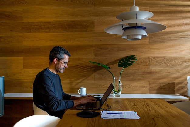 Homme d'affaires travaillant avec un ordinateur portable dans son salon