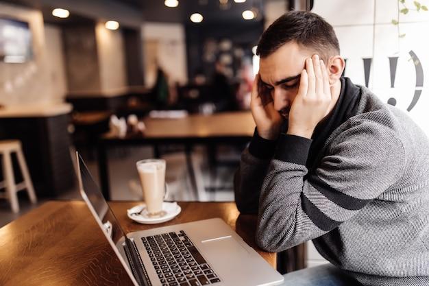 Homme d'affaires travaillant à l'ordinateur portable avec mal de tête dans un café sur la terrasse.