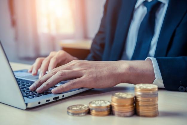 Homme d'affaires travaillant avec des pièces de monnaie. concept de croissance des investissements et d'économies d'argent.