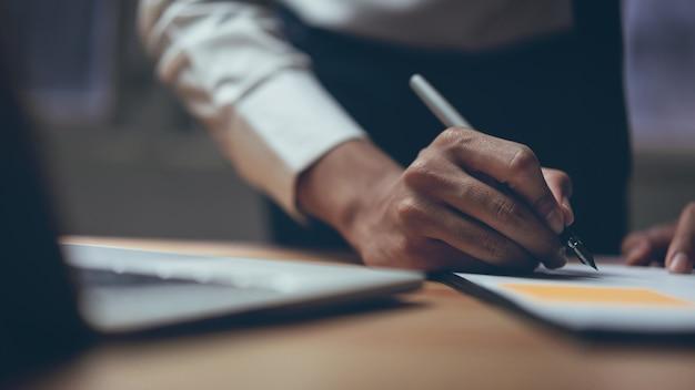 Homme d'affaires travaillant avec un projet de démarrage en coworking. utilisation de plans marketing sur ordinateur portable.