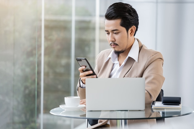 Homme d'affaires travaillant avec un smartphone et un ordinateur portable