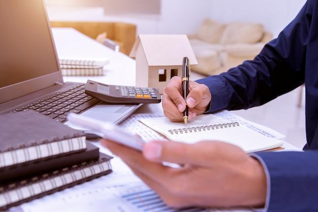 Homme d'affaires travaillant sur son bureau dans le bureau avec une calculatrice, un document.