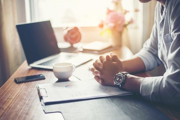 Homme d'affaires travaillant sur son bureau avec une tasse de café au bureau.
