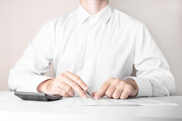 Homme d'affaires travaillant à table avec stylo et calculatrice sur blanc
