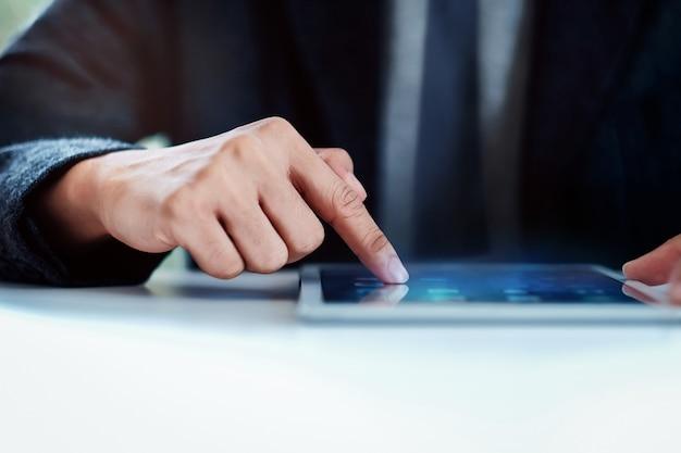 Homme d'affaires travaillant sur une tablette numérique dans le bureau au bureau. mise au point sélective et image recadrée
