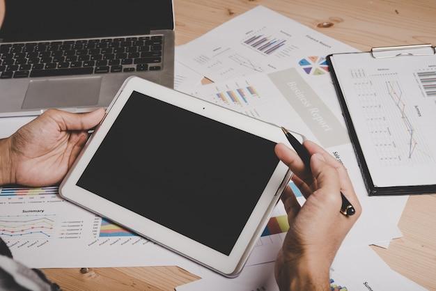 Homme d'affaires travaillant avec tablette numérique vierge et ordinateur portable sur bureau en bois dans le bureau.