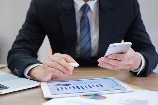 Homme d'affaires travaillant sur tablette et smartphone et ordinateur portable sur le bureau