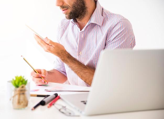Homme d'affaires travaillant avec un téléphone portable et un ordinateur portable