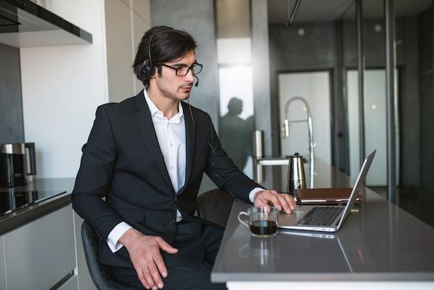 Homme d'affaires travaille à distance à la maison avec un ordinateur portable