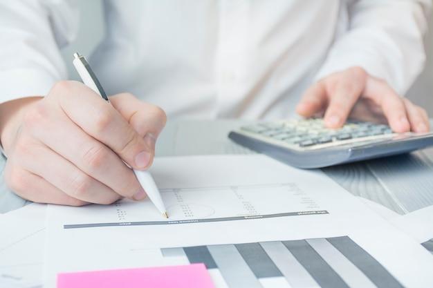 Homme d'affaires travaille avec des papiers. gros plan des mains d'un homme qui travaille. travaillez avec les chèques, les taxes et les factures. idée de génie. objectifs d'affaires