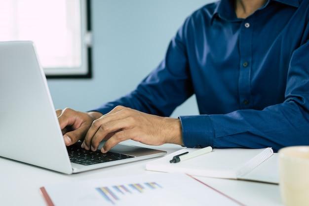 Homme affaires, travailler, ordinateur portable, à, graphique, diagramme, document, rapport, cahier, bureau