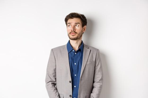 Homme d'affaires triste réfléchi en costume regardant le coin supérieur gauche