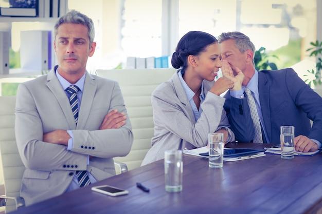 Homme d'affaires triste regardant ailleurs pendant que ses collègues parlent
